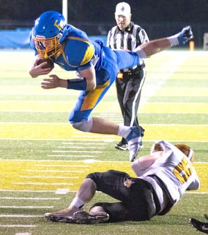 East Canton quarterback Chase Vacco jumps over Tusky Central's Thayne Mahaffy.