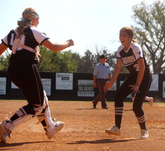 Lone Grove's Emma Wilson, right, waits to give Chloe Yeatts a hug following the final out Friday in an 18-0 win over Ada.