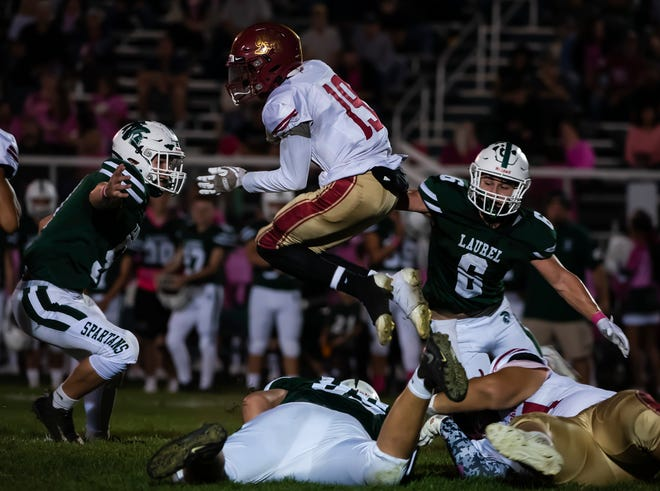 New Brighton's Gary Pugh tries to leap over Laurel defenders during their game Friday at Laurel High School,[Lucy Schaly/For BCT]