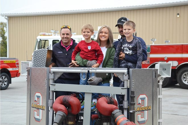 Firefighter Shane Heldstab gives a ladder truck ride to Thomas and Tristan Brekken, kids of firefighter Derek Brekken and Michelle Brekken who are stationed overseas, and Nissa Brekken and Ethan Magsam.
