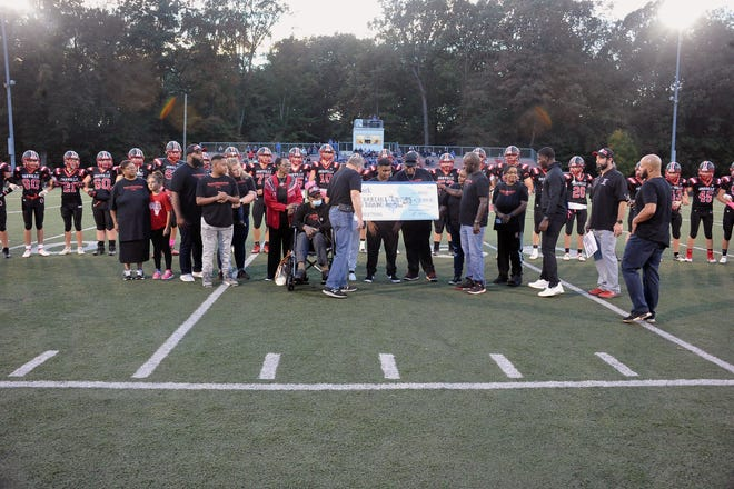 Orrville Mayor Dave Handwerk and city councilman Darrell  Mosley presented Drayedon Williams, center, with a check for $10,000 toward hospital expenses before Friday's home football game against CVCA..  Williams was joined by family members Paul M. DeHart, Forence DeHart, June Gaines, Ticarris Williams, Tandris Williams, Santana Williams, Lorasen Stowers, Paula DeHart-Williams and Marvin Williams.
