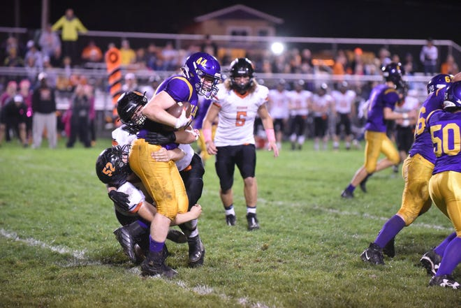 Hudson's Logan Swallows (52) takes down Blissfield's Chase Collyer during Friday's game at Blissfield.