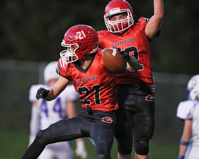 Clinton's Nik Shadley (21) and Joey Preston celebrate a touchdown during Friday's game against Dundee. [Telegram photo by John Discher]