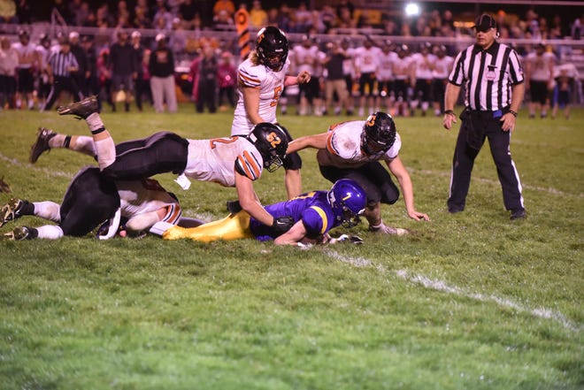 Hudson's Cameron Kimble (62) and Logan Swallows take down Blissfield's Noah Schnoor during Friday's game at Blissfield. [Telegram photo by Deloris Clark-Osborne]