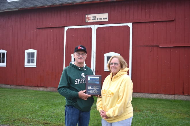 """Palmyra Township residents Tom and Kathy Eisenmann stand in front of their Rouget Road """"Party Barn"""" Saturday morning while holding a plaque awarded to them Sept. 27 from the Michigan Barn Preservation Network. The Eisenmanns' barn, which has been in the family for years, was one of five Michigan barns named a """"Barn of the Year"""" this year."""