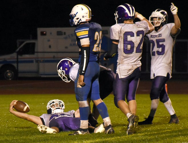 Little Falls Mountie Mason Rowley raises the ball in celebration after scoring the winning touchdown in overtime Friday at Mt. Markham.