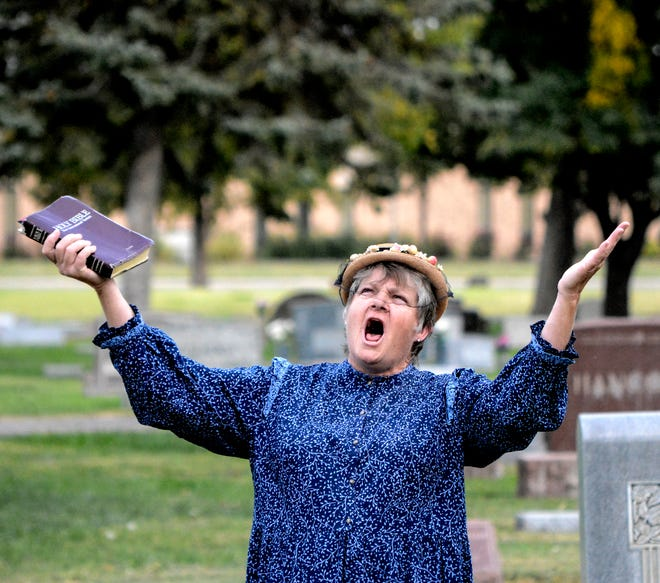 Annie Fleagle, portrayed by Synthia Preston, defends her family to visitors during a stop on a Finney County Historical Society's Historic Walking Tour of Valley View Cemetery Friday evening. The cemetery tours, featuring volunteer re-enactors portraying individuals from Finney County's history, is in its eighth year. Fleagle is the mother of gangsters, Jake and Ralph Fleagle, members of the Fleagle Gang.