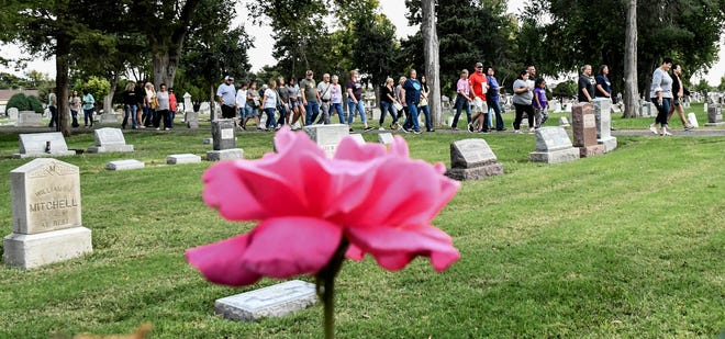 A group on one of the Finney County Historical Society's Historic Walking tours make their way along one of the roads in Valley View Cemetery Friday evening to the next re-enactor.