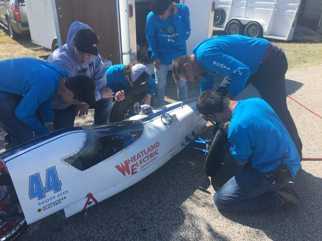 Members of the Scott City pit crew work to change a flat tire on one of the team's cars at Thursday's electric car rally at Frontier Park.