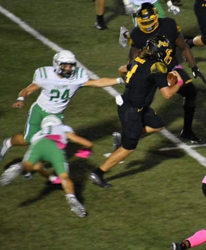 Denison's Caleb Heavner runs away from a pair of Lake Dallas defenders during the Yellow Jackets' victory in District 7-5A (II) action at Munson Stadium.