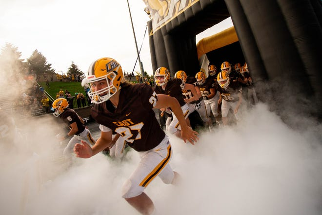 The Zeeland East varsity football team rushes onto the field for their homecoming game against Wyoming Friday, Oct. 8, 2021 at Zeeland Stadium.