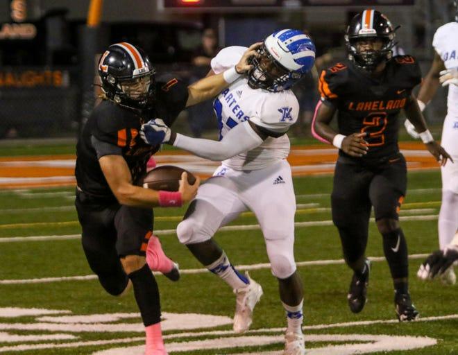 Lakeland quarterback Mason Martin stiff-arms an Apopka defender en route to a big gain on Friday night at Bryant Stadium.