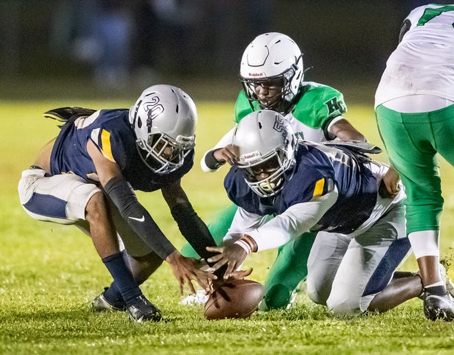 Ridge Community's Ty Footman (20) and Trenton Herrington (50) scoop up the fumble by Haines City's Rocky Pieriche (10) during first half action at Ridge Community in Davenport.