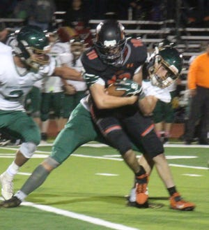 La Junta High School's Ian Backes attempts to break free from a Manitou Springs tackler after a big gain.