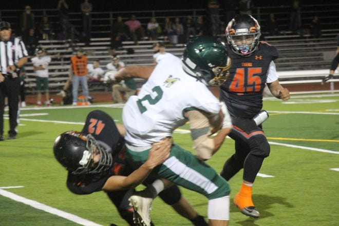 La Junta High School's Keo Fisher (42) tackles Manitou Springs' Tate Christian while Andrew Raso comes to assist. The Tigers defeated the Mustangs 60-27 on Oct. 8 at Tiger Stadium.
