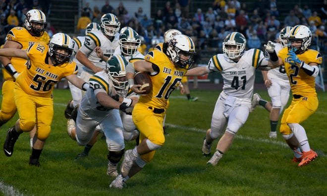 Erie Mason's Aiden McMullen runs for a long gain getting away from Tommy Perkey of Sand Creek Friday night.