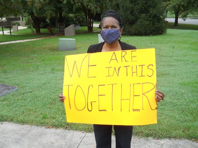 Oak Ridge resident Valeria Roberson holds a sign stating, 'We are in this together,' at an event promoting vaccines and thanking healthcare workers and other first responders for their efforts.