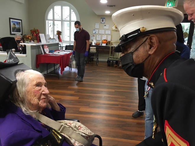 Marine Corps veteran of the Vietnam War and Purple Heart recipient Lewis Alston, right , congratulates Helen Bonomini on her 100th birthday Friday at Brookdale Paddock Hills assisted living facility in Ocala. Bonomini served in the Marines Women's Reserves in World II. The party was held Friday to mark her milestone birthday, which is Sunday (Oct. 10).