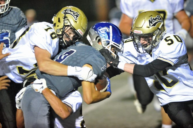 North Kingstown's Dan McKay (left) and William Draper (right) help gang-tackle Cumberland's Evan Spencer during the first quarter of the Skippers' win over the Clippers.