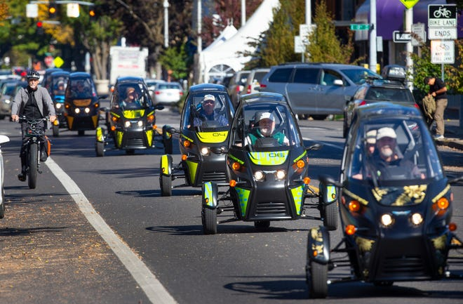 """Supporters of electricvehicles parade through Eugene in Arcimotos and other electricvehicles for """"PlugIn to a Clean Future,"""" a campaign to bring awareness to the impact of fossil fuel consumption on the environment."""