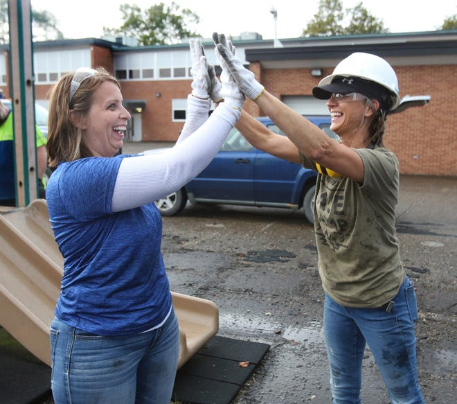 Melissa Glover, left, and Diane Vandersall celebrate successfully tossing playground equipment into a dumpster at the Compton Learning Center in Canton on Saturday, Oct. 9, 2021.