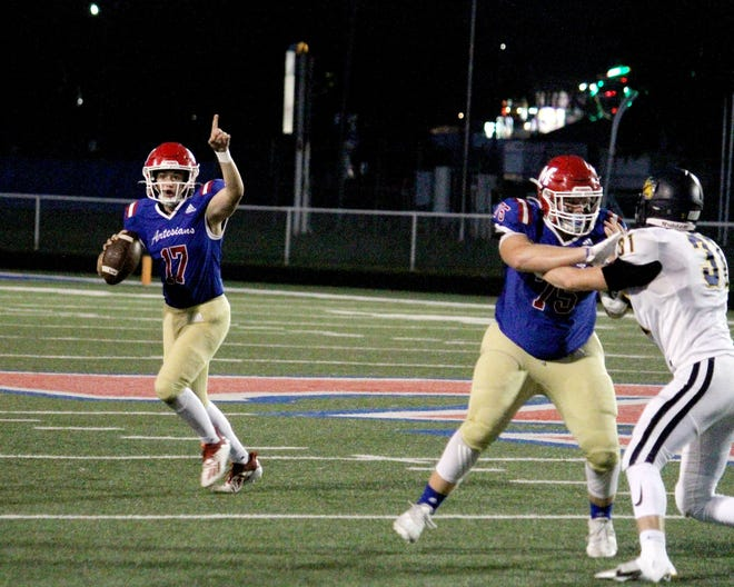 Martinsville junior quarterback Tyler Adkins tells his receiver to go down field during Friday's Mid-State Conference game and senior night against Mooresville.