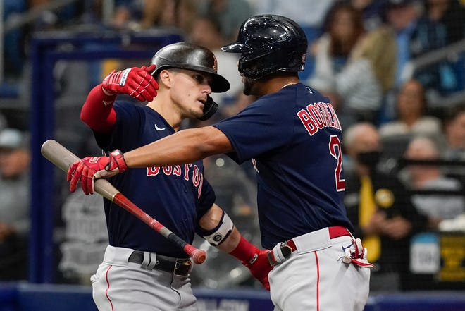 Boston Red Sox's Enrique Hernandez, left, celebrates his solo home run against the Tampa Bay Ray with Xander Bogaerts (2) during the fifth inning in Game 2 of a baseball American League Division Series in St. Petersburg, Fla.