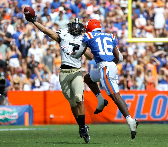 Florida Gators safety Tre'Vez Johnson (16) leaps up to target Vanderbilt Commodores wide receiver Cam Johnson (7) as he throws the ball on a gadget play during a football game between the Florida Gators and the Vanderbilt Commodores at Ben Hill Griffin Stadium in Gainesville, Fla. October 9, 2021.