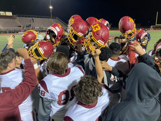 The Barstow football team breaks from a huddle after beating Adelanto in overtime at Julian Weaver Stadium on Oct. 8, 2021.