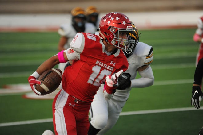 Sweetwater senior Joeangel Reyna runs past a Snyder defender on Friday at the Mustang Bowl. Sweetwater was able to hold off its rival 42-37.