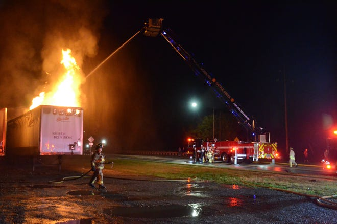 Battle Creek firefighters pour water on a burning semi trailer Friday. (Contact Trace Christenson/The Enquirer)