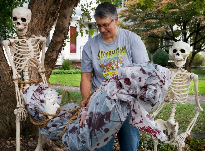 """Ann Dixon arranges her """"Skeleton Crew""""  in front of her home on South Lombard Avenue in Evansville, Ind., Thursday morning, Oct. 07, 2020."""