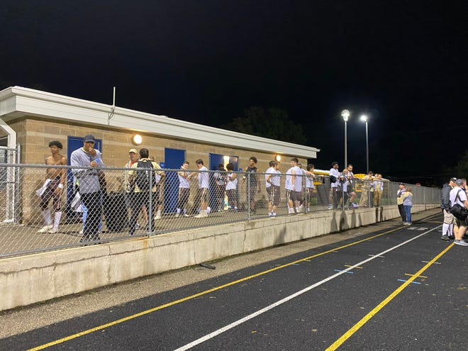 Holt football players wait out a lightning delay on Friday, Oct. 8, 2021, at East Lansing High School.