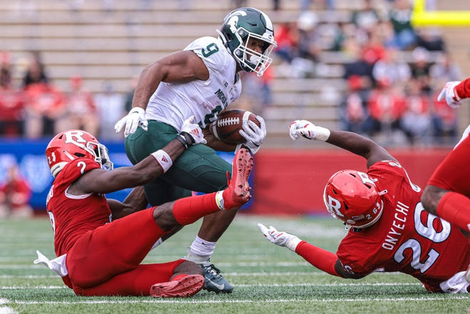 Oct 9, 2021; Piscataway, New Jersey, USA; Michigan State Spartans running back Kenneth Walker III (9) is tackled by Rutgers Scarlet Knights defensive back Avery Young (2) and defensive lineman CJ Onyechi (26) during the second half at SHI Stadium.