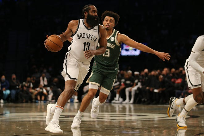 Nets guard James Harden works against Jordan Nwora (13) of the Bucks during the second quarter Friday at Barclays Center during their exhibition game. Nwora led all scorers with 30 points. Harden finished with eight points.