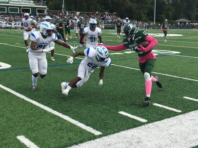 DePaul's De'zie Jones (13) fights for extra yardage as Irvington's Raheem Wright (28) and Vaboue Toure (21) try to force him out of bounds.