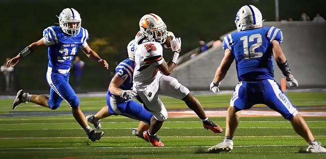 Central York sophomore running back Juelz Goff, center, carries the ball against a trio of Spring Grove defenders on Friday. Central York won the game, 48-17.