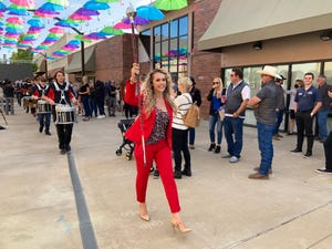 Redding Mayor Erin Resner leads the Foothill High School drum line to the food truck court in Carnegie Park after Friday's State of the City event under Umbrella Alley.