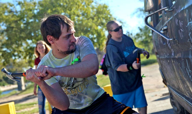 Aaron Wilson, left, wields a hammer during the Smash the Stigma Rally at the San Angelo Clubhouse on Saturday, Oct. 9, 2021.