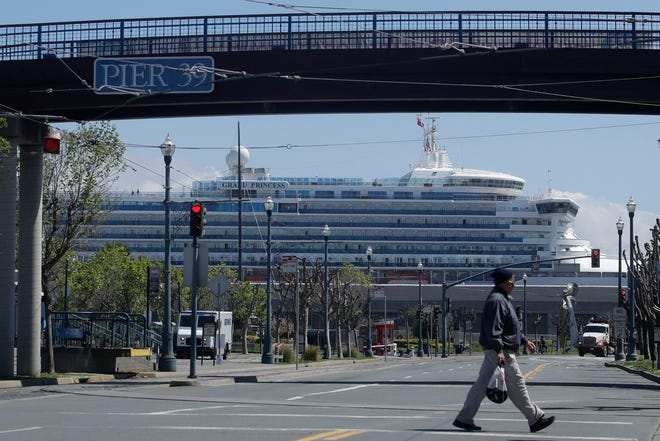 The cruise ship terminals are near some of the most famous landmarks in San Francisco, including Fisherman's Wharf, Pier 39 and the Ferry Building. In this April 7, 2020, file photo, a man crosses the street under a pedestrian bridge at Pier 39 as the Grand Princess cruise ship, rear, is shown docked at Pier 35 in San Francisco.