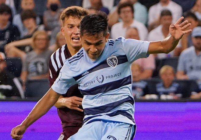 Sporting Kansas City midfielder Felipe Hernandez (front) kicks a shot on goal as Colorado Rapids defender Keegan Rosenberry defends.