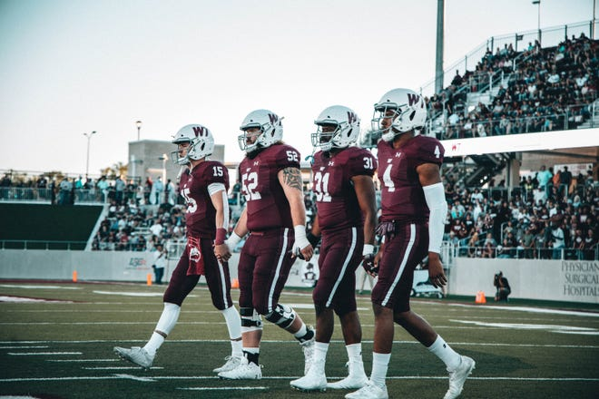 West Texas A&M captains Nick Gerber (15), Zane Madison (52), Christopher Thomas (31), and Eric Collins (4) approach midfield before the game against Angelo State at Buffalo Stadium on Saturday, Oct. 9, 2021.