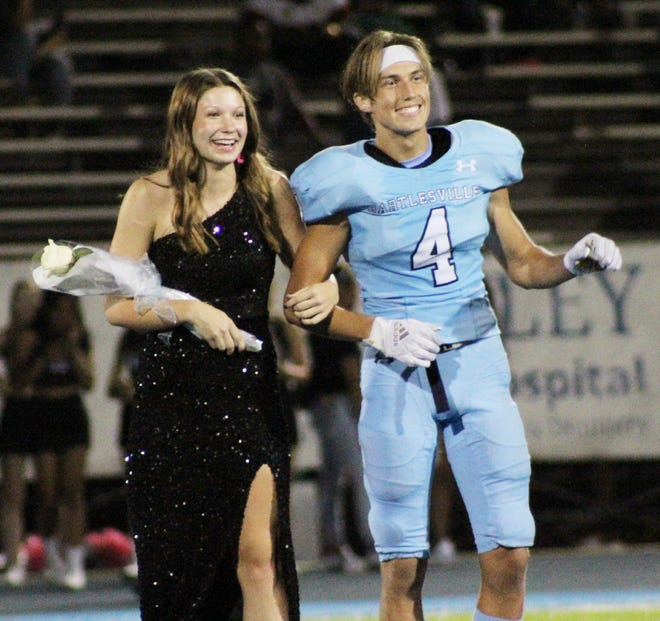 Logan Vaclaw escorts Sydney Collins across the field during halftime ceremonies at Bartlesville High's Homecoming game Friday night. Vaclaw, the king, plays defensive back for the Bruins and Collins, the queen, is a four-year varsity starter for the Bruins volleyball team.