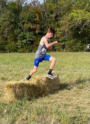 Boonville's Hayden Williams jumps over hay bales during the Capital City Invitational Saturday at Binder Lake Park in Jefferson City. Williams finished 28th out of 40 runners in a time of 21:15.
