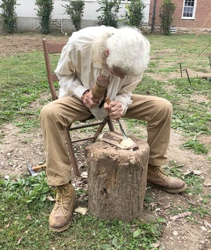 A wood carver chisels out a piece of wood during the 53rd annual Arrow Rock Heritage Festival Saturday in downtown Arrow Rock.