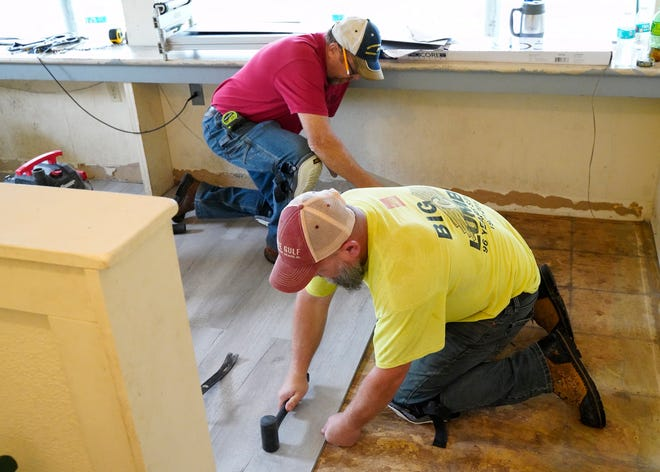 """Bob Gardner, wearing a red shirt, the owner of RDG Carpentry in Adrian, and Tim Kudlac of Blissfield work Friday on replacing the press box floor at O.W. Farver Memorial Park in Blissfield. The reconstruction work was a part of Midwest Energy & Communication's annual """"Day of Action"""" volunteer event."""