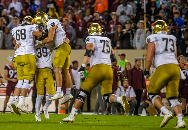 Notre Dame players run to Irish kicker Jonathan Doerer (39) to celebrate after his game-winning field goal during ND's 32-29 win over Virginia Tech on Saturday, Oct. 9, 2021, in Blacksburg, Va.