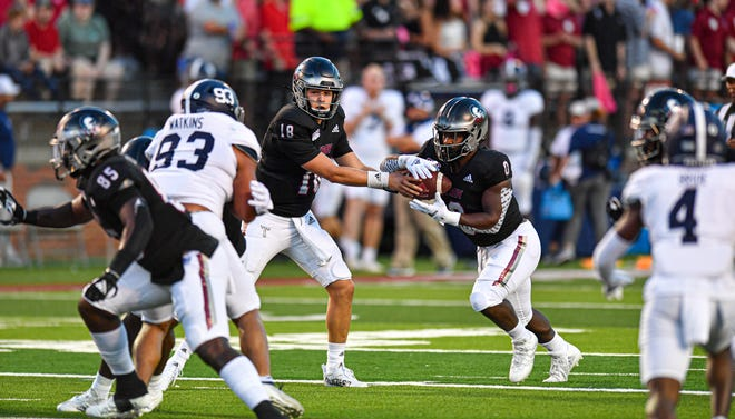 Troy quarterback Gunnar Watson (18) hands off to running back Kumani Vidal (0) for a play against the Georgia Southern defense on Saturday night in a  Sun Belt Conference game in Troy, Alabama.