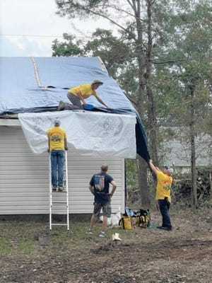 A crew tarps a damaged roof  in Mandeville.