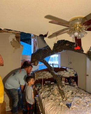 Jimmy Harper looks at a tree that fell through a bedroom during Hurricane Ida.